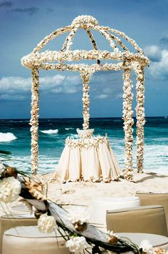 An altar of seashells, carnations and starfish awaits the bride and groom at the edge of the water.