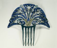 Spectacular evening party comb, of flecked celluloid, enhanced with bright blue paste stones and underlined with gold in the middle