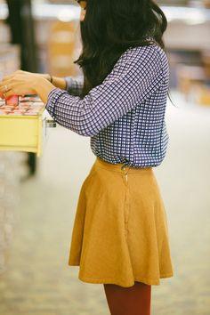 Checkered top, yellow skirt.