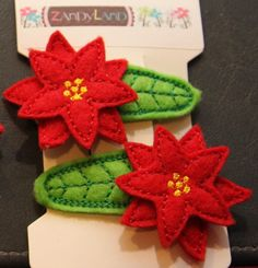 Set of two machine embroidered poinsetta felt stitchies snap barrette hair clips.   http://www.etsy.com/listing/86597112/red-poinsetta-felt-stitchies-snap