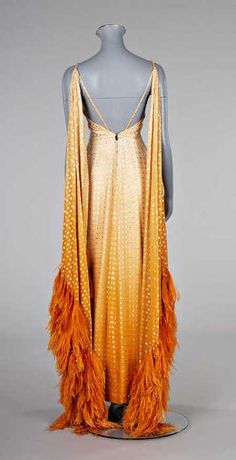 This unique orange evening dress with feather details is from Pierre Balmain in 1970.