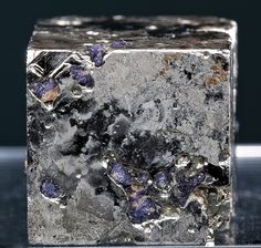 A shiny Pyrite cube with inclusions of purple Fluorite