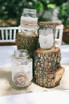 rustic centerpieces ... decorated mason jars perched a top tree stumps | Jennifer Martin Photography | Glamour & Grace