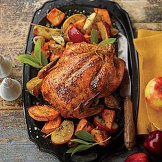 Grill-Roasted Chicken | Grilling over the indirect heat of a two-zone fire mimics oven heat. An aromatic rack of early fall apples and vegetables catches all the chicken's flavorful juices. | SouthernLiving.com
