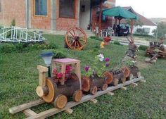Outdoor wooden train made from tree stumps and filled with flowers