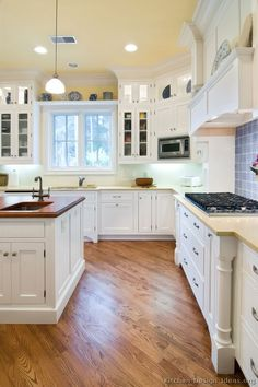 A lovely cottage kitchen with white cabinets, wood floors, and a beautiful wood hood...     #3 in Traditional White Kitchen Cabinets