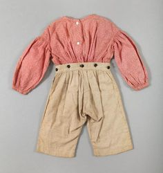 Boy's outfit, pink and red calico shirt attached to plaid tan blue and gray patterned pants, hand-sewn, cotton and wooden buttons, circa 1840.