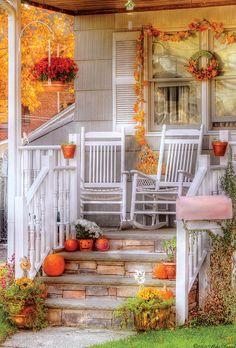 Beautiful white porch with rocking chairs - decorated for Autumn #outdoor #landscaping #fall #pumpkins