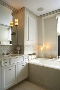 I'm in love with this bathroom! Love the niche with towels, trim tile, crown molding, sconces over mirror...clean and crisp yet soft and romantic
