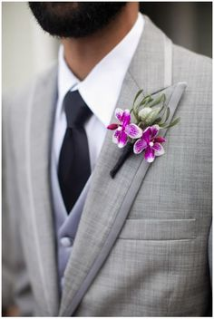 Bright purple orchid boutonnieres don the groomsmen's jackets.  Flowers by Ingela Floral Design. Photographer: Tim Halberg