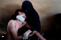 """Fotografía del español Samuel Aranda, ganadora del World Press Photo del año 2011, elegida entre más de 100 mil imágenes. Contrasta el negro del """"niqab"""" (un velo islámico que cubre todo el rostro a excepción de los ojos) con el cuerpo desnudo del joven herido que está en los brazos de la mujer, luego de una manifestación en Yemen."""