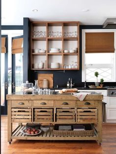 Kitchen with navy walls, white trim, wood shelves, rustic island with crate drawers and bamboo blinds.