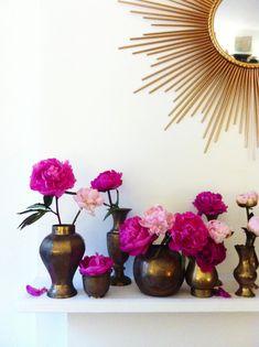 Lonny market editor Cat Dash arranges pink peonies in vintage brass vessels on her mantel. floral interior, color schemes, mantel, pink flowers brass, pink peonies