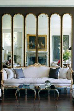 Decorating with dark paint doesn't mean you'll end up with a room of Stygian gloom. In fact the very opposite. Used properly drama and atmosphere await. Like this living room with large antique mirrors.