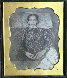 Example of a post mortem photo where eyes have been painted onto the girls eyelids so it appears her eyes are open and that she is alert. She is holding a book as if she's been reading.