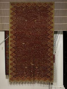Rug, c.1920. Wavy, weed like flowers and ears of corn closely packed across the carpet. Scattered between them are birds, butterflies, insects, mushrooms and geometric motifs. The carpet is lined with a border consisting of a row of truncated lozenge shapes each lined with stiff flower heads containing a single plant. Single plants also decorate the interstices between the lozenges and the outer edge of the carpet. The flowers are in shades of green, white, blue, pink and red ofr a field of...