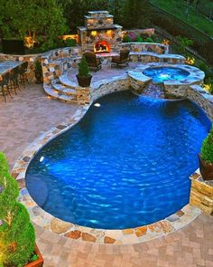 Stoned patio with built in pool and hot tub that cascades into the pool. Also a patio, fire place and bar area for entertaining