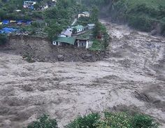 Houses perch precariously as river banks collapse from the rising waters of the flooded river in the northern state of Uttarakhand on June 17, 2013 Posted by floodlist.com #floods #uttarakhand