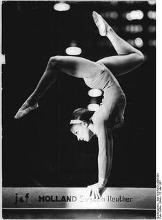 Gymnast Erika Zuchold performing handstand on balance beam (1967).