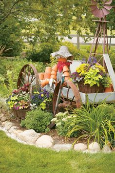 Man made of containers in a Wagon Planter. Love the scene with old windmill and old wagon wheels on the wagon in middle of flower bed!!