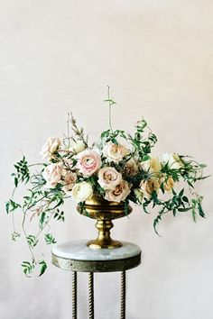 Muted taupe colored rose, ranunculus, and vine centerpiece by Sarah Winward, photo by Leo Patrone