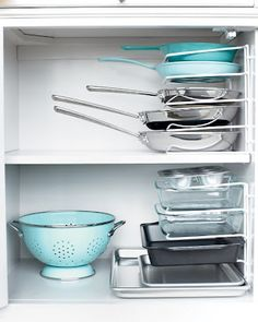 Just use a vertical bakeware organizer on it's end and secure it to your cabinet with cable clips. This can also be used for frying pans.