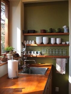 Open shelving, avocado green walls, restaurant style crockery & glassware, wood counter tops