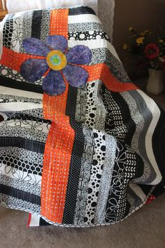 Black and white quilt with a bold dash of color.