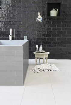 Black bathroom with grey bath and white floor. Tiles from vtwonen collection