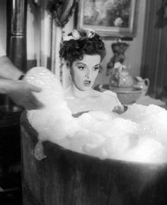 Jane Russell in a bath tub full of bubbles