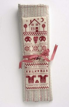 Cross-stitch knitting themed sampler on a knitting needle case.  Pattern designed by Helen Phillips, available through The Making Spot