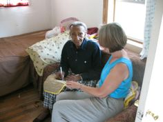 QUILTER, ALLIE PETTWAY   |  Ms. Allie Pettway (on left) signs a quilt sample in her Gees Bend Home.  (photo: (on right)  Maria Gitin, Author, Civil Rights Veteran, 1965 Wilcox County Freedom Fighter, speaker on voting rights).  (2008)