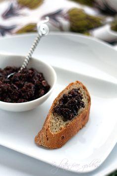 Vegan olive tapenade (appetizer spread) on a gluten-free baguette slice.