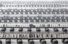 Pilgrims and devotees cross pontoon bridges at the Maha Kumbh Mela - the largest spiritual gathering on the planet, held every 12 years in India. (© Wolfgang Weinhardt, 2014 Sony World Photography Awards)