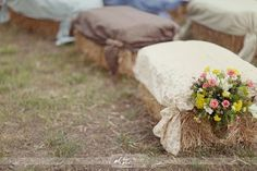 Fabric covered hay bale seating - padding for comfort topped by simple drapes of fabric secured on each corner with a small bunch of flowers, such as lavender, is a charming country idea!!