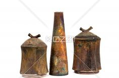 old long metal vase arranged in between of rusted containers with lid. - Image of old long metal vase arranged in middle of rusted containers with lid on top of each one.