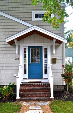 Exterior paint idea.  Want something neutral with a surprising door color.  Then incorporate that color into the garden and porch.  Blue? Teal? Bright orange?