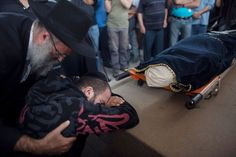 KIRYAT MALACHI, ISRAEL: A relative grieves during the funeral for Itzik Amsalem, 49, one of the three people who died in a rocket attack on Nov. 16, 2012 in Kiryat Malachi, Israel. Three people were killed in Israel Nov. 15, after a building was hit by a rocket fired from the Hamas-ruled Gaza Strip. Palestinian rocket attacks followed a series aerial strikes on targets in Gaza launched by Israeli Defense Forces (IDF) which killed a top military commander of Hamas. (Uriel Sinai - AFP/Getty Images
