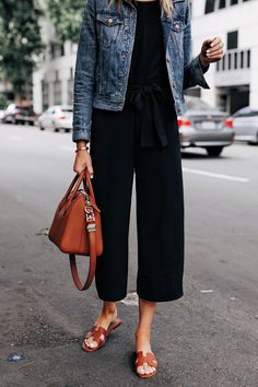 Fashion Jackson Wearing Everlane Black Jumpsuit Denim Jacket Tan Sandals Tan Tote