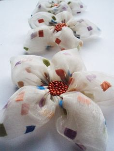 Flowers made from colorful squares over cream fabric.