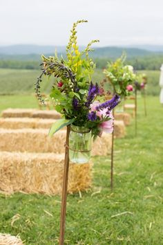 Hay bale pews, mason jars attached to antique tobacco sticks full of our flowers...sunny Summer wedding! Life is good at Pharsalia