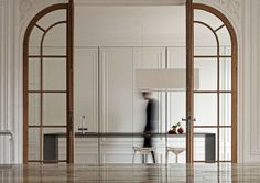 INVISIBLE KITCHEN,  i29 designed a Paris kitchen that acts more as a piece of furniture instead of as a kitchen.  Large sliding wall panels with moldings conceal all kitchen appliances and storage space. glass doors, invis kitchen, i29 architect, interior architect, i29 interior