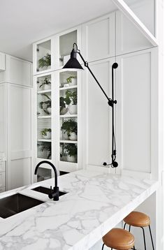 white kitchen carrera marble black sconce tan leather stools