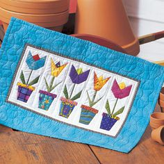 Quilt designed by Leisa Breheny.Size: 17 1/2' x 11 1/2'The bright tulips in this adorable wallhanging seem to pop off the fabric.  Foundatio...