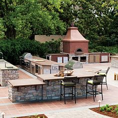 outdoor kitchen complete with bar seating, fireplace & maybe a woodfired oven