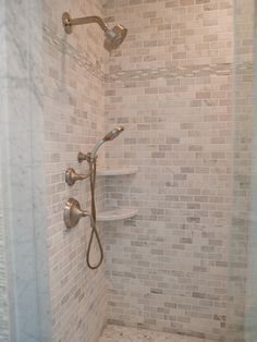 Asian Statuary Marble Subway Tile with a Glass Mosaic Detail. A brushed nickel double shower head pairs beautifully with the marble tile work.