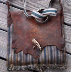 Very Primitive Rustic Mountain Man Possibles Bag. Made of black walnut stained, vintage ticking cloth with distressed leather flap. Strap is inkle loomed linen/ cotton, with elk antler closure. or by Miss Tudy, $115.00