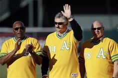 Hall-of-Famer Rollie Fingers, center, waves to fans between former Oakland Athletics teammates Vida Blue, left, and Gene Tenace before a baseball game between the Athletics and the Cleveland Indians, Saturday, April 21, 2012, in Oakland, Calif. The former A's were gathered for a reunion of the 1972 team. (AP Photo/Ben Margot)
