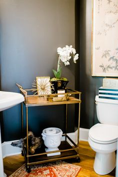 A repurposed bar cart looks great in this beautiful powder room! | Photography: Caroline Lima Photography - www.carolinelima.com  Read More: http://www.stylemepretty.com/living/2014/09/02/behind-the-blog-emily-a-clark/