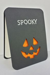handmade Halloween card .... black card base ... negative die cut Jack-o-Lantern face exposes orange glitter paper like  a glowing candle on the inside ... great clean and simple design ...